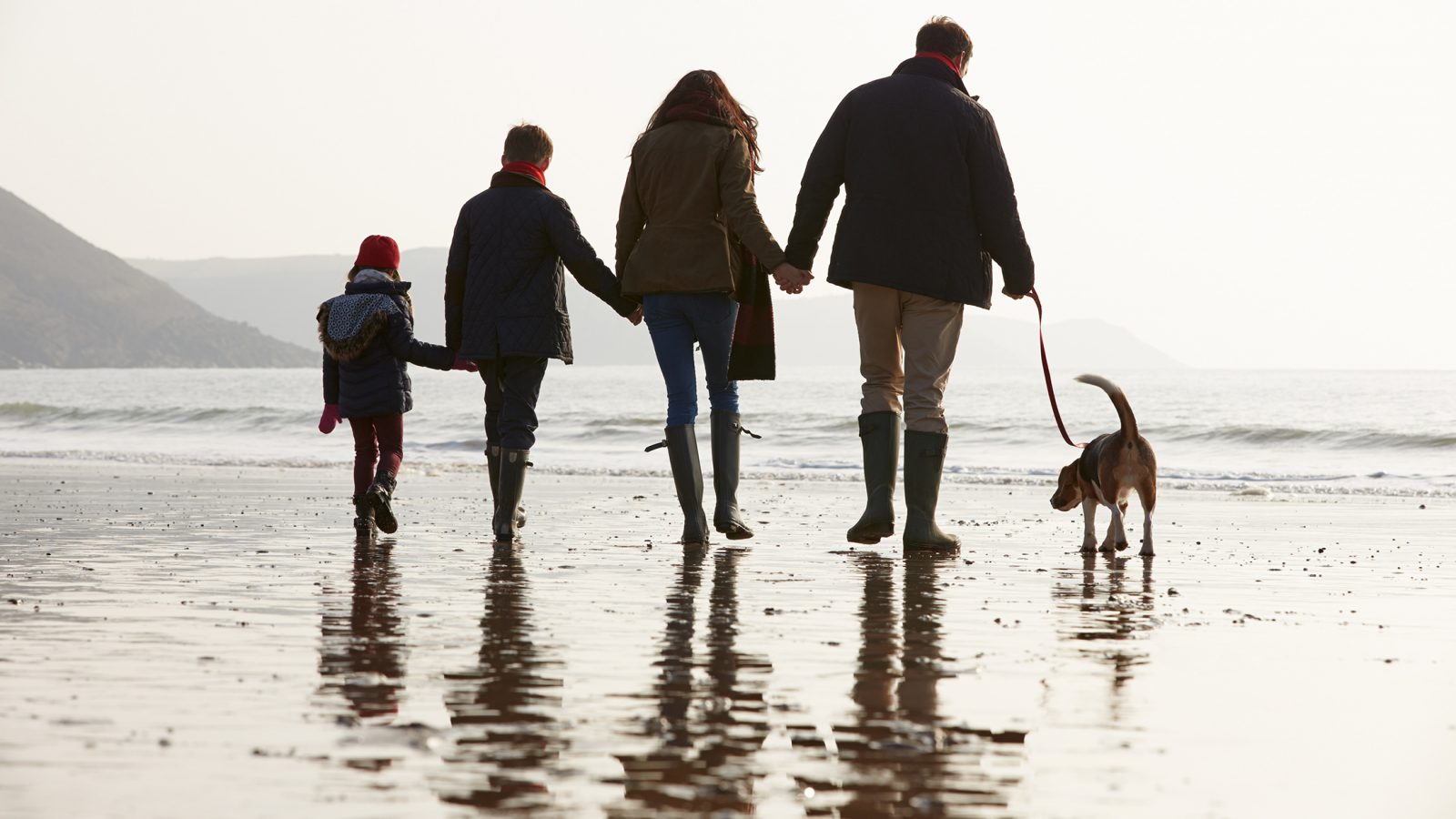 Family walking dog on the beach