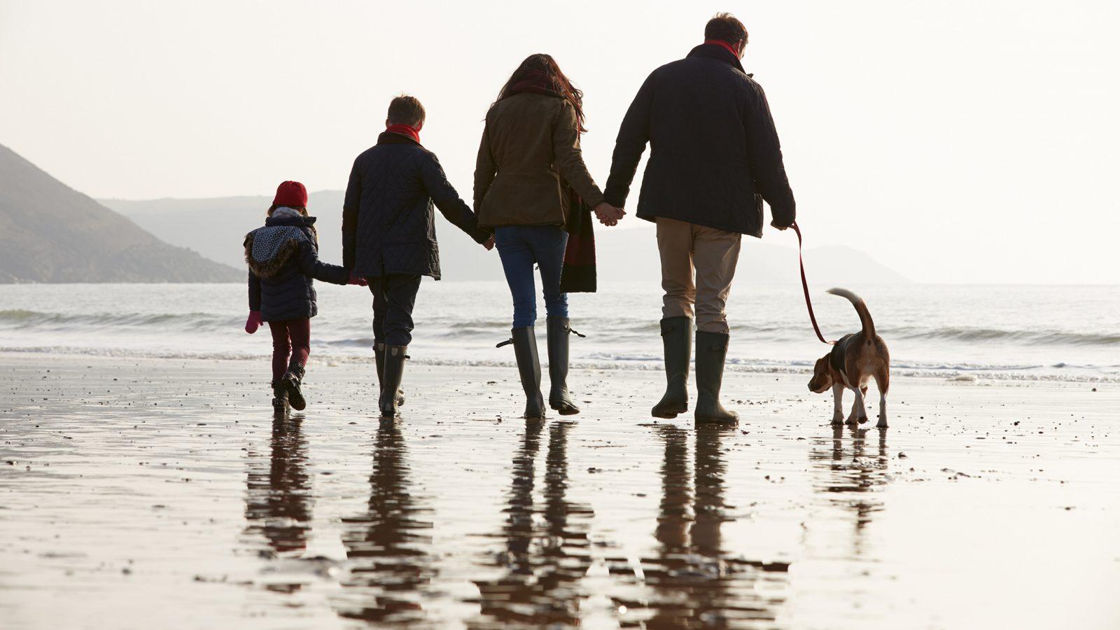 Family walking dog on the beach